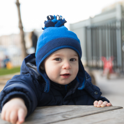 Infant in JCC Beautiful Beginnings program sitting at a picnic table wearing winter clothes