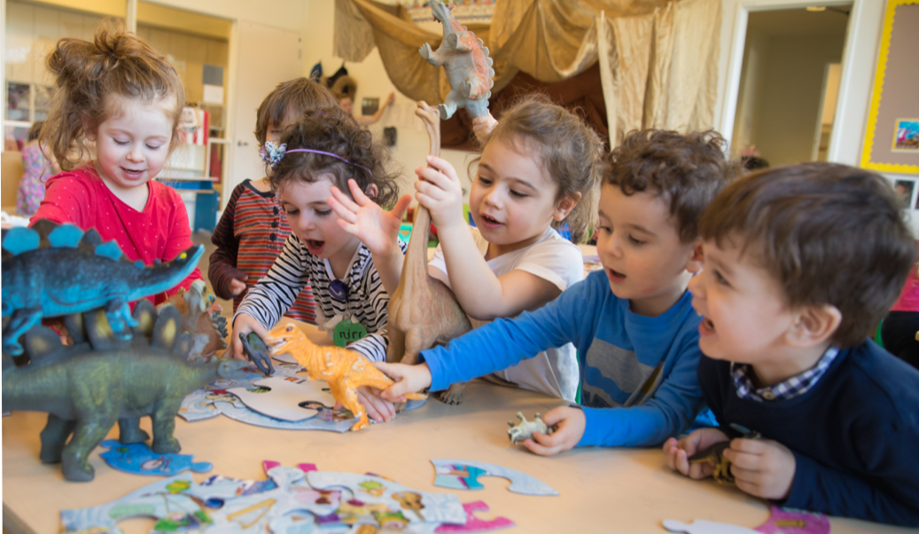 Children at a table in Preschool classroom playing together with toy dinosaurs