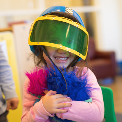Child in JCC daycare program smiling and wearing a helmet and holding dress up clothes