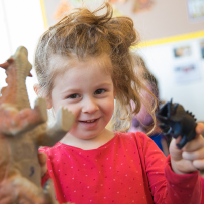 Toddler in Little Learners program playing with toy dinosaurs
