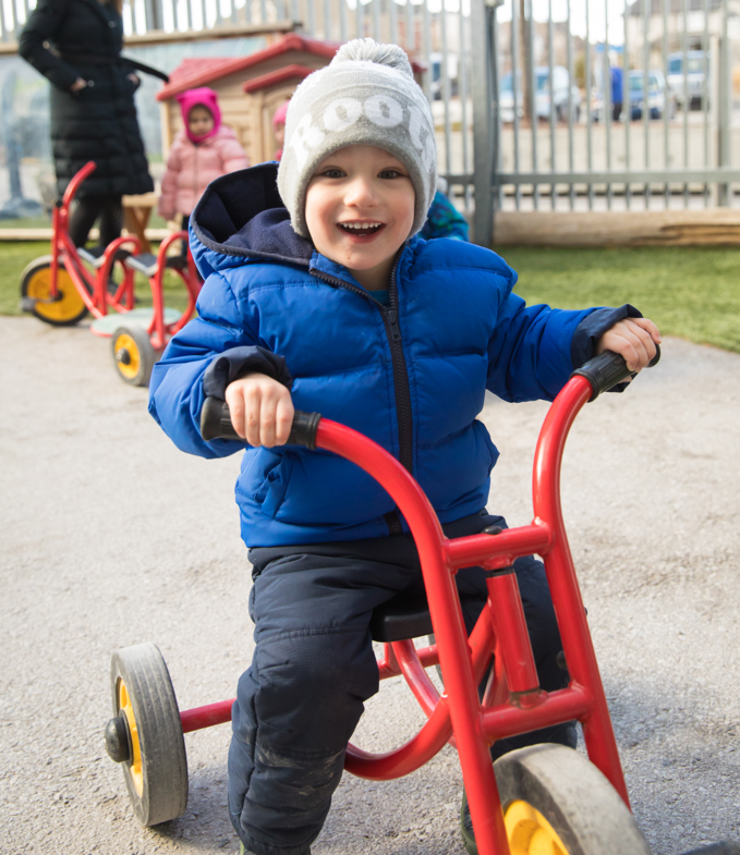 Child in the JCC daycare program riding on a tricycle
